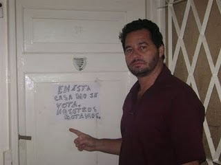 "Ángel Santiesteban pointed to his ""oddly"" slanted handwriting. The sign says: In this house we don't vote. We toss it out."
