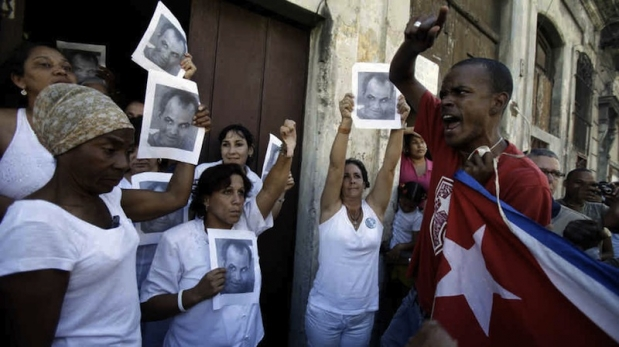 A Castro goon harassing a group of Ladies in White holding posters of the former political prisoner Orlando Zapata Tamayo who died in prison on a hunger strike.