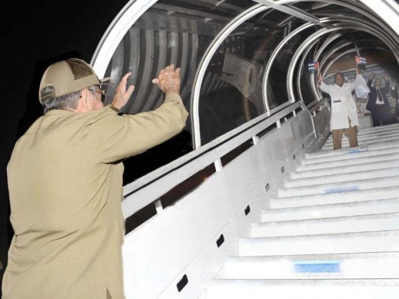 Raul Castro waves goodbye to a Cuban healthcare worker leaving for an overseas post
