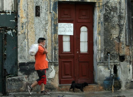 A man with a pack over his shoulder walks down a Havana street.