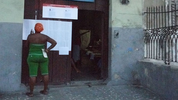 A woman checks the list of candidates for the municipal elections. (14ymedio)