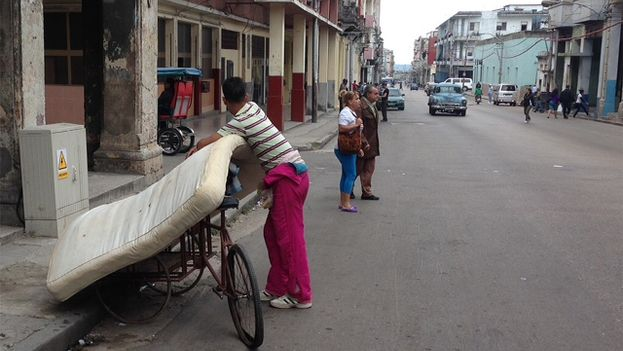 A man places a mattress on a bicycle in a street of Havana. (14ymedio)