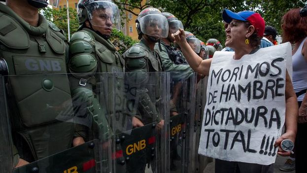 A woman protests against members of the Bolivarian National Guard in the march on Wednesday in Caracas. (EFE / Miguel Gutierrez)