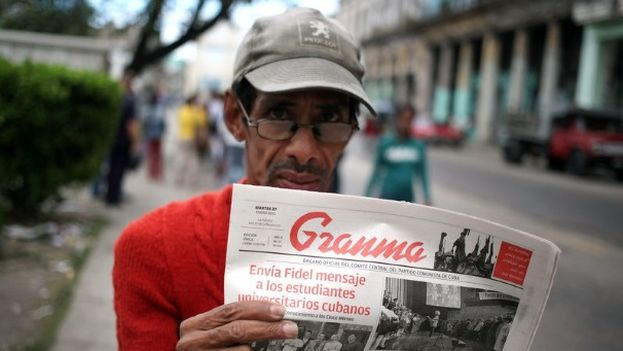 "A man holds up an edition of the official daily Granma, from 2015. Headline: ""Fidel sends a message to Cuban university students."" (EFE)"