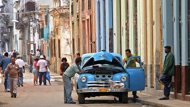 "Cubans try to repair an ""almendrón"" (old American car) in Havana. (SN)"