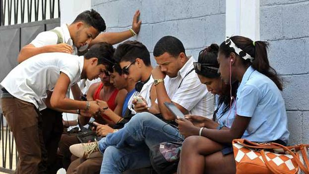 A group of young people connect to the internet in a wifi zone in Havana. (EFE)