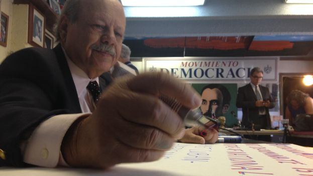 A Democracy Movement activist prepares posters for the protest against American Airlines. (14ymedio)
