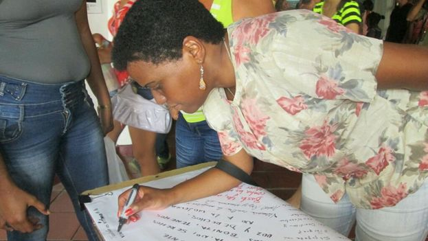 Zuleica Romay, President of the Cuban Institute of the book, writing a message against gender-based violence. (Y. MAYEYA)