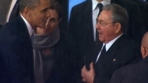 Raul Castro and Barack Obama greet each other for the first time at the funeral of Nelson Mandela in South Africa