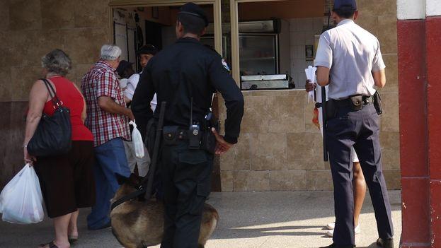 A policeman checks a street vendor's papers and merchandise (Reinaldo Escobar / 14ymedio)