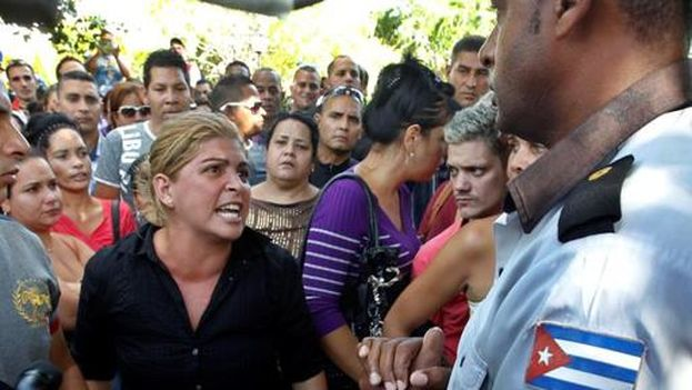 Woman argues with uniformed Cuban agent in front of the Ecuadorian embassy in Havana