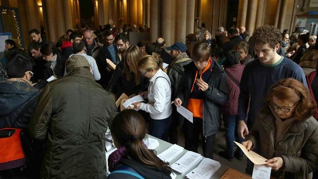 Citizens choose ballots to exercise their vote in elections at the polling station located at the University of Barcelona. (EFE / Toni Albir)