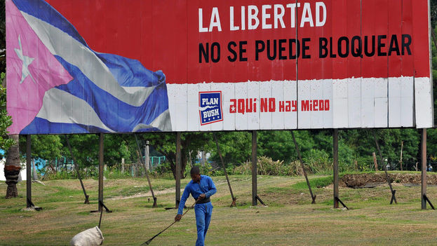 A worker sweeps in front of a propagandistic ad in Havana (EFE). The ad reads: Liberty Cannot Be Blockaded/Here There Is No Fear
