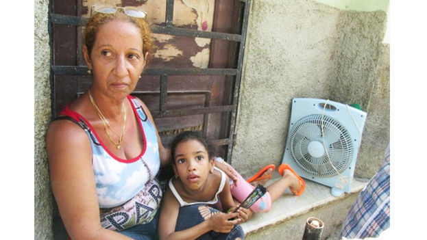 Denise Rodriguez Cedeño with one of her granddaughters, says she would rather sleep in the street for fear that the roof of her house will fall in. (14ymedio)