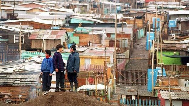 Some children observe their homes in the commune of Peñalol east of Santiago de Chile. (EFE)