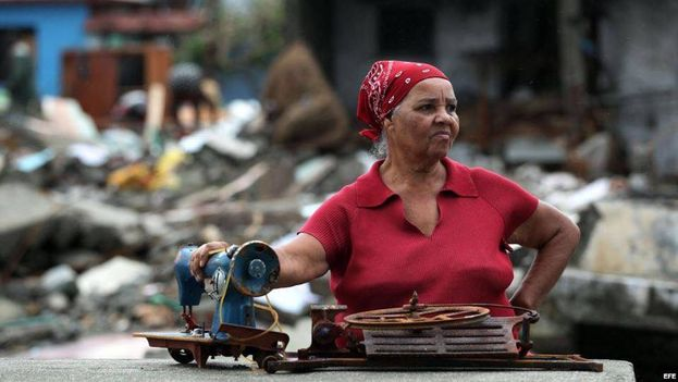 A woman holds her sewing machine amid the desolation left by Matthew in Baracoa. (EFE)